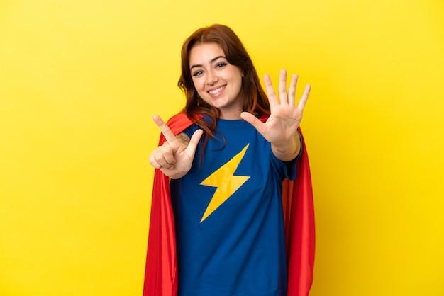 Mujer pelirroja de superhéroe aislada sobre fondo amarillo contando siete con los dedos