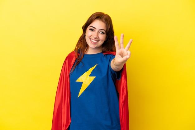 Mujer pelirroja superhéroe aislada sobre fondo amarillo feliz y contando tres con los dedos
