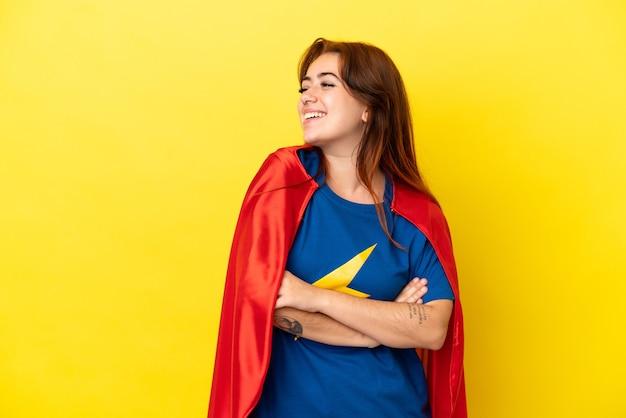 Mujer pelirroja superhéroe aislada sobre fondo amarillo feliz y sonriente