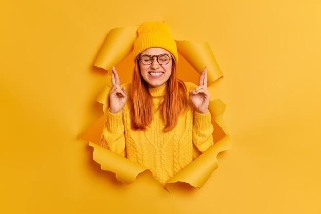 La mujer pelirroja supersticiosa aprieta los dientes y cruza los dedos con la esperanza de que los sueños se hagan realidad, usa un sombrero amarillo y un suéter se rompe a través del agujero de papel la chica millennial de jengibre cree en la buena suerte. concepto de deseo