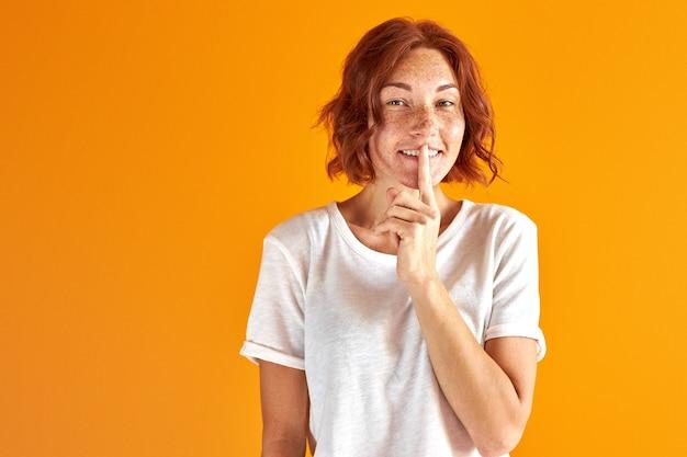 Mujer pelirroja tiene un secreto, muestra el gesto de guardar silencio, sonríe mirando a la cámara sobre naranja