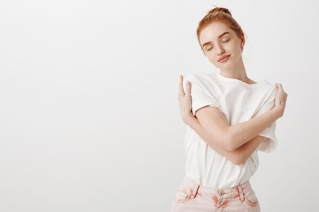 Mujer pelirroja tierna soñadora abrazando su propio cuerpo con los ojos cerrados