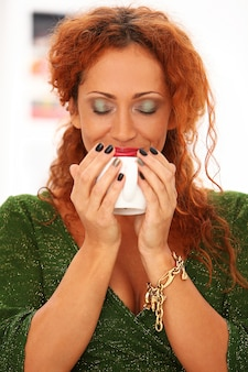 Mujer pelirroja tomando café