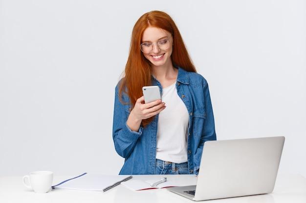 Mujer pelirroja trabajando en proyecto con teléfono inteligente, de pie cerca de la computadora portátil