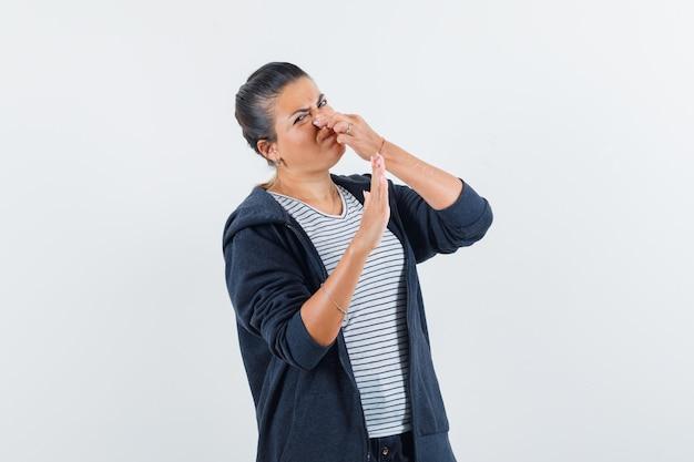 Mujer pellizcando la nariz debido al mal olor en camiseta