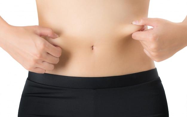 Mujer pellizcando el vientre y la barriga grasa aislado sobre fondo blanco.
