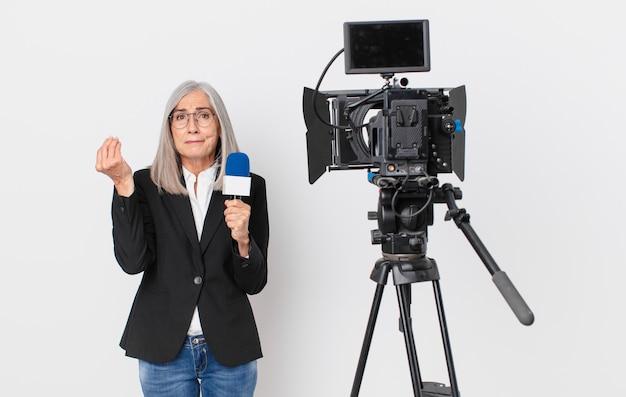 Mujer de pelo blanco de mediana edad haciendo capice o gesto de dinero, diciéndole que pague y sosteniendo un micrófono. concepto de presentador de televisión