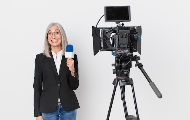 Mujer de pelo blanco de mediana edad que parece feliz y gratamente sorprendida y sosteniendo un micrófono. concepto de presentador de televisión