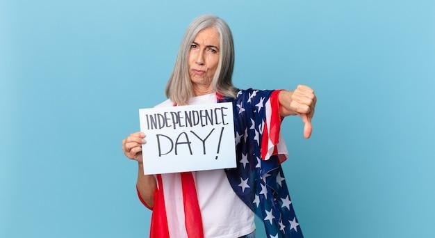 Mujer de pelo blanco de mediana edad que se siente cruzada, mostrando los pulgares hacia abajo. concepto del día de la independencia