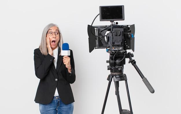 Mujer de pelo blanco de mediana edad que se siente feliz, emocionada y sorprendida y sosteniendo un micrófono. concepto de presentador de televisión