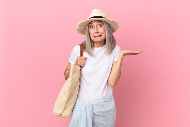 Mujer de pelo blanco de mediana edad que se siente perpleja, confundida y dudando. concepto de verano