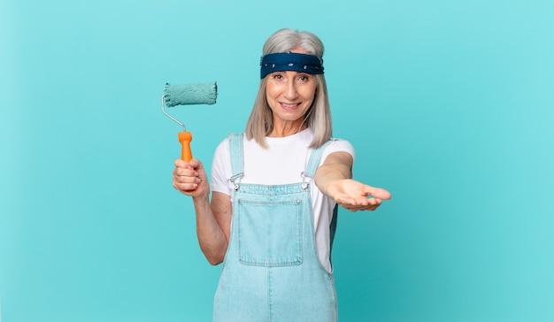 Mujer de pelo blanco de mediana edad sonriendo felizmente con amable y ofreciendo y mostrando un concepto con un rodillo pintando una pared