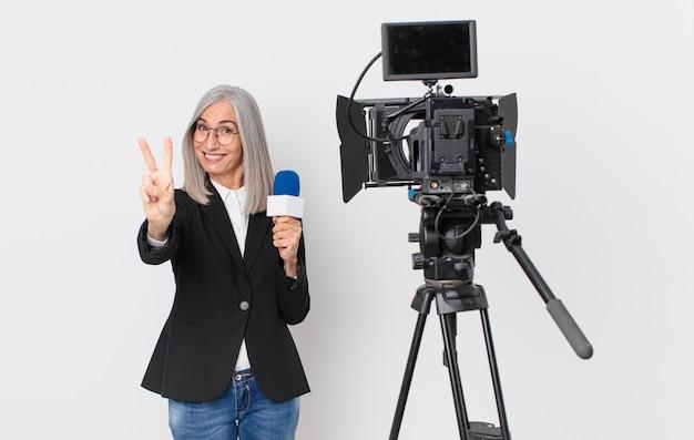 Mujer de pelo blanco de mediana edad sonriendo y mirando feliz, gesticulando victoria o paz y sosteniendo un micrófono. concepto de presentador de televisión