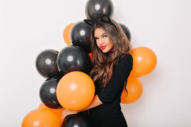 Mujer de pelo castaño en elegante vestido posando con globos de halloween