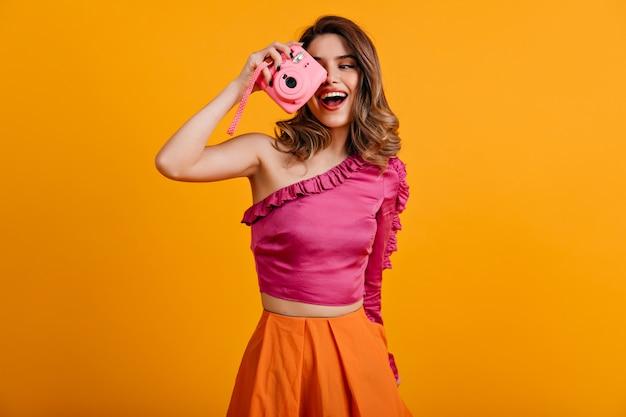 Mujer de pelo castaño rizado haciendo fotos con sonrisa