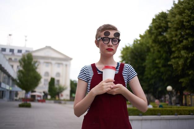 Mujer con pelo corto en la calle con gafas de vidrio con bebida a pie