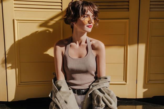 Mujer de pelo corto con gafas de sol posando en puertas amarillas. mujer rizada en camiseta con chaqueta mira hacia otro lado en puertas amarillas