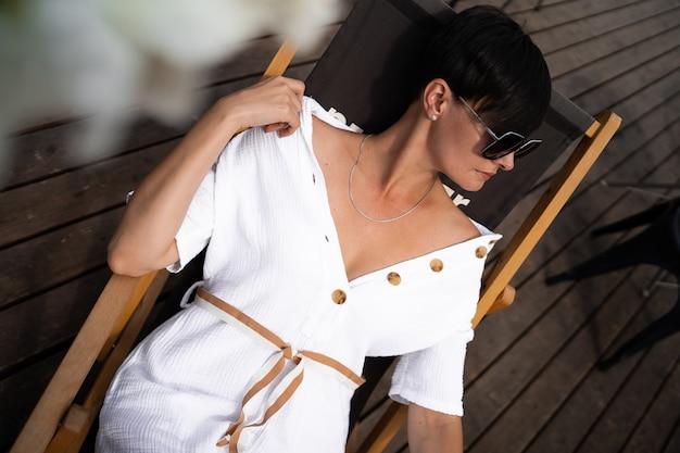 Mujer con el pelo corto y morena con ropa blanca y gafas de sol fotografía callejera de moda. modelo de moda está sentado y relajarse en el fondo de madera marrón.