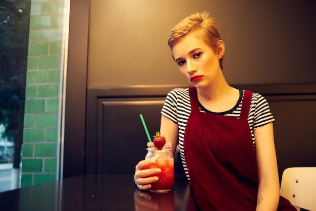 Mujer con pelo corto sentado en el estilo de vida de vacaciones de cóctel de café