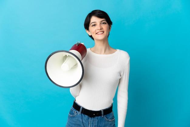 Mujer con pelo corto sosteniendo un megáfono y sonriendo mucho