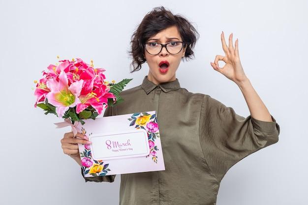 Mujer con pelo corto con tarjeta de felicitación y ramo de flores mirando a cámara confundida y sorprendida haciendo bien firmar celebrando el día internacional de la mujer el 8 de marzo de pie sobre fondo blanco.