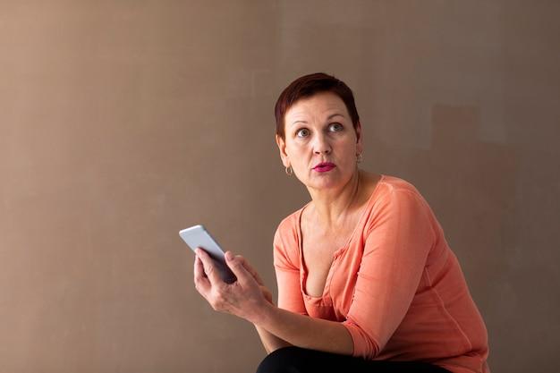 Mujer de pelo corto con teléfono mirando a otro lado