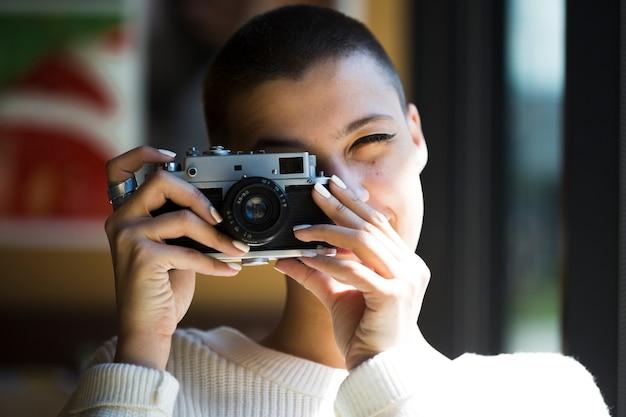 Mujer de pelo corto tomando foto con cámara vintage