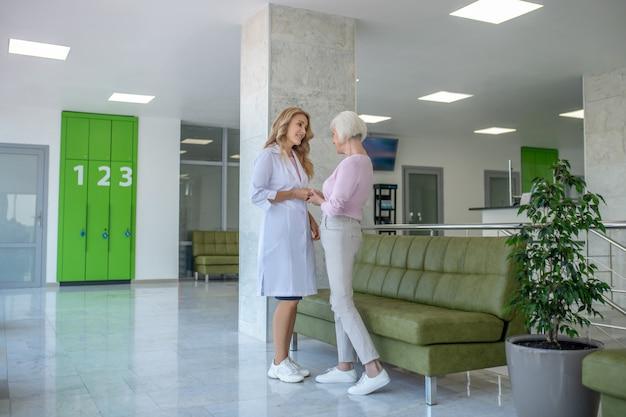 Mujer de pelo gris hablando con el médico en el pasillo de la clínica