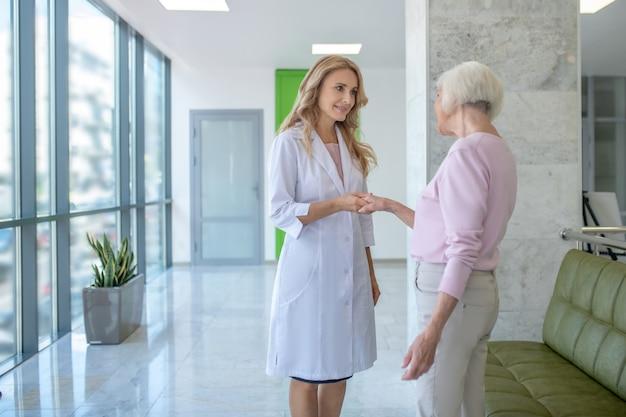 Mujer de pelo gris que se encuentra con el médico en la clínica
