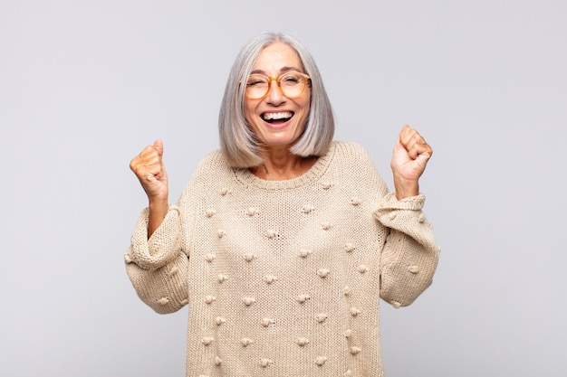 Mujer de pelo gris que parece extremadamente feliz y sorprendida, celebrando el éxito, gritando y saltando