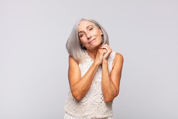 Mujer de pelo gris que se siente enamorada y se ve linda, adorable y feliz, sonriendo románticamente con las manos al lado de la cara