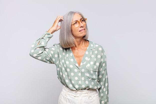 Mujer de pelo gris que se siente perpleja y confundida, rascándose la cabeza y mirando hacia un lado