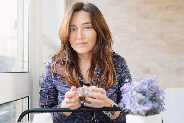 Mujer de pelo largo bebiendo su café o té de la mañana en un balcón.