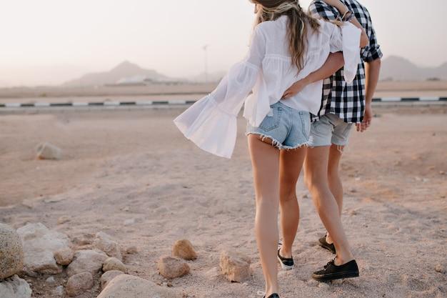 Mujer de pelo largo con chico en pantalones cortos de mezclilla de moda camina en un abrazo cerca de la carretera temprano en la mañana. elegante pareja abrazándose y disfruta de hermosas vistas al desierto en una cita en la noche de verano.