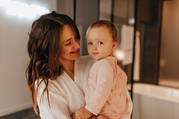 Mujer de pelo largo positiva en bata blanca con tierna sonrisa mira a su pequeña hija.