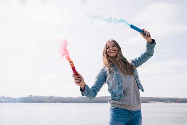 Mujer de pelo largo sonriente sosteniendo bombas de humo de colores