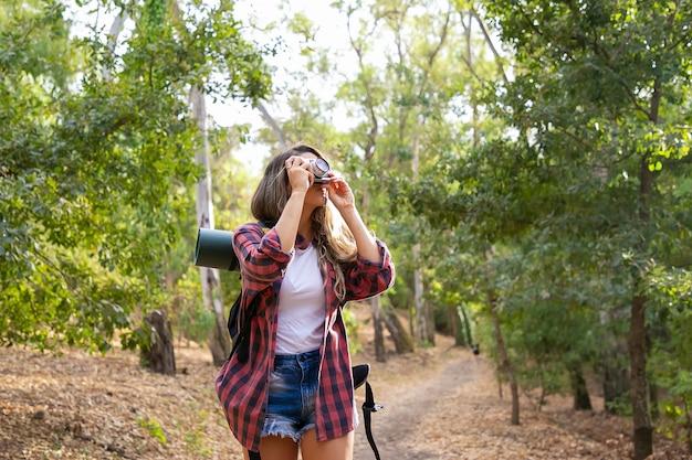 Mujer de pelo largo tomando fotos de la naturaleza y de pie en la carretera en el bosque. señora caucásica rubia que sostiene la cámara y el paisaje de tiro. turismo de mochilero, aventura y concepto de vacaciones de verano.