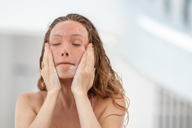 Mujer del pelo ondulado que aplica la loción de bronceado de la protección solar en su cara, concepto de la protección del cuidado de piel.
