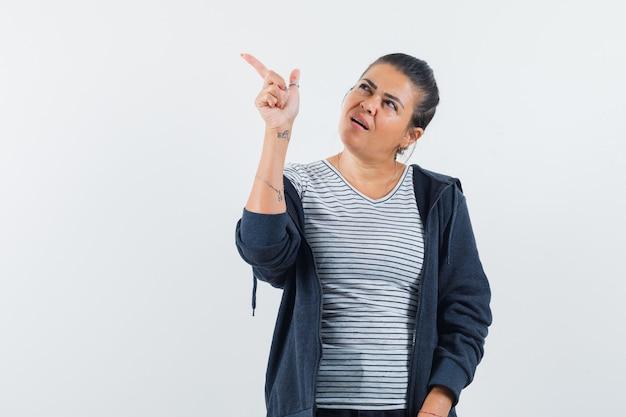 Mujer de pelo oscuro apuntando lejos en camisa