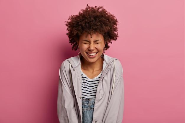 La mujer de pelo rizado, alegre y sincera, tiene una sonrisa brillante con dientes, disfruta de la vida sin problemas, se ríe de las bromas divertidas, entrecierra los ojos con placer, usa anorak informal, posa sobre una pared rosada.