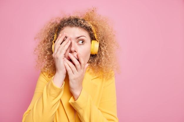 Mujer de pelo rizado asustada se siente muy asustada cubre la cara mira hacia otro lado