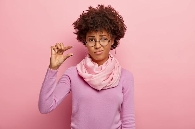 Mujer de pelo rizado molesta da forma a un pequeño gesto, demuestra algo muy pequeño, usa gafas ópticas, jersey informal y bufanda