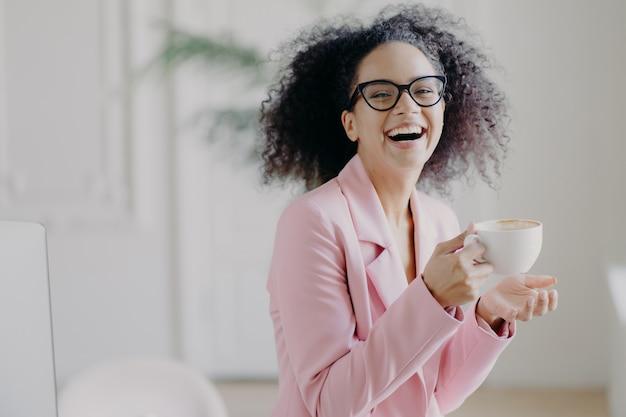 Mujer de pelo rizado muy contenta ríe alegremente mientras bebe café caliente