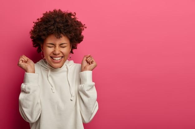 Mujer de pelo rizado optimista despreocupada levanta los puños cerrados