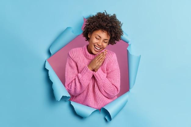 La mujer de pelo rizado optimista sincera mantiene las palmas juntas juntas ríe de alegría expresa emociones naturales usa poses de suéter de punto a través de la pared rasgada de papel