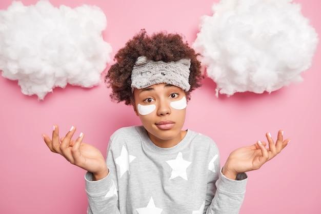 La mujer de pelo rizado vacilante extiende las palmas siente dudas vestida con ropa de dormir aplica parches de colágeno debajo de los ojos para eliminar las ojeras viste ropa de dormir aislada sobre una pared rosa con nubes arriba