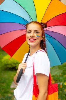 Mujer de pelo rojo con bandera lgbt en su rostro posando con paraguas de arco iris