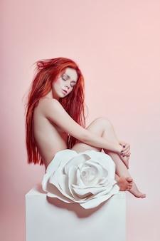 Mujer con pelo rojo sentada flor de papel grande