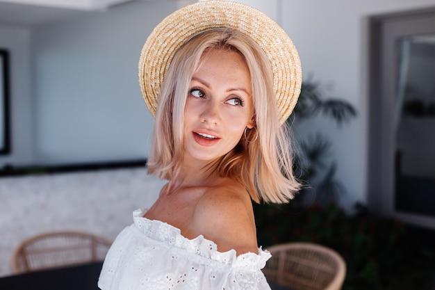 Mujer de pelo rubio bastante caucásico joven en la cocina al aire libre en la villa