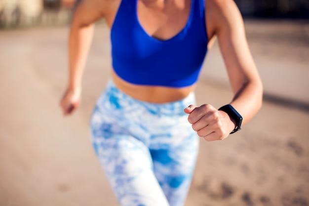 Mujer con el pelo rubio corto corriendo al aire libre. de cerca. concepto de personas, fitness y salud